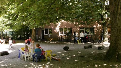 INA.KINDER.GARTEN Rosenheimer Straße, Außengelände mit Kindern auf Stühlen